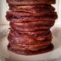Homemade beet pancakes dab with butter and drizzled with maple syrup.
